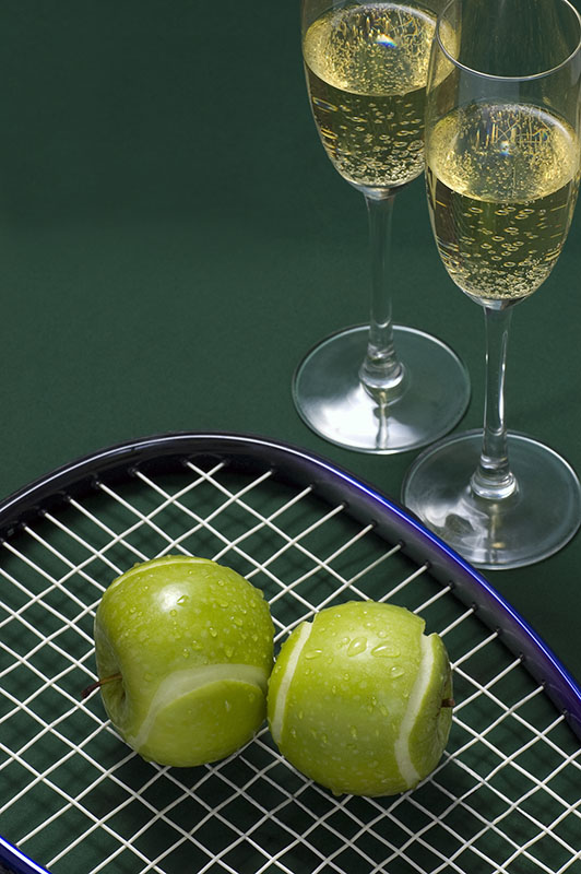 apples cut to look like tennis balls placed on a tennis racquet with two glasses of champagne