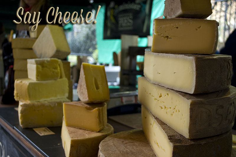market stall selling wheels and quarters of cheese all stacked up