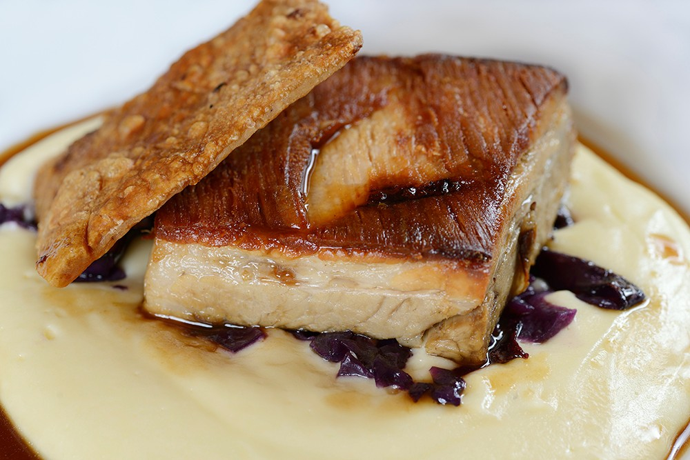 Pork belly with mash potato, red cabbage and an apple jus. on a white plate