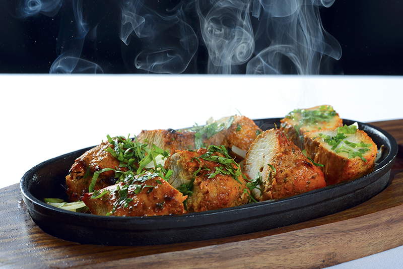 chicken tikka pieces on a hot plate