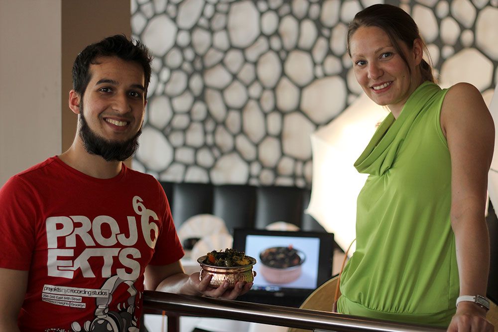 man holding pot of curry next to woman with photo of the curry on a laptop in the background