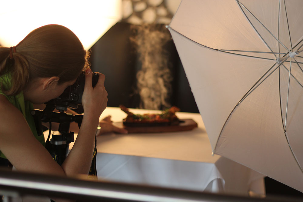 female photographer photographs hot food on a sizzler plate steam is visible