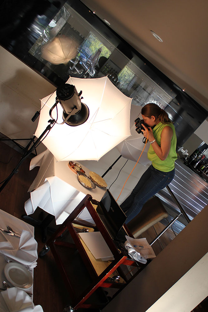 female food photographer photographing food whilst standing on a chair