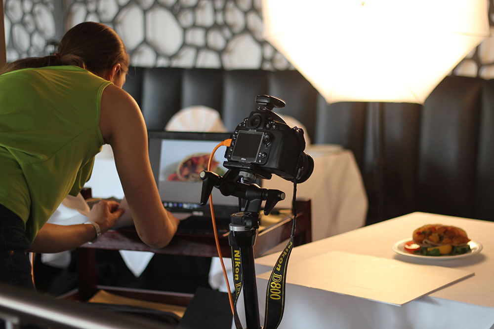 female photographer checks photograph on a laptop there is a camera on a tripod in front of plate of food
