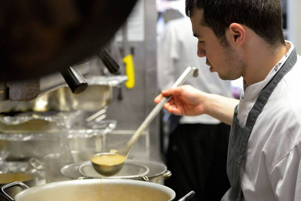 Chef checking stock in a large pot