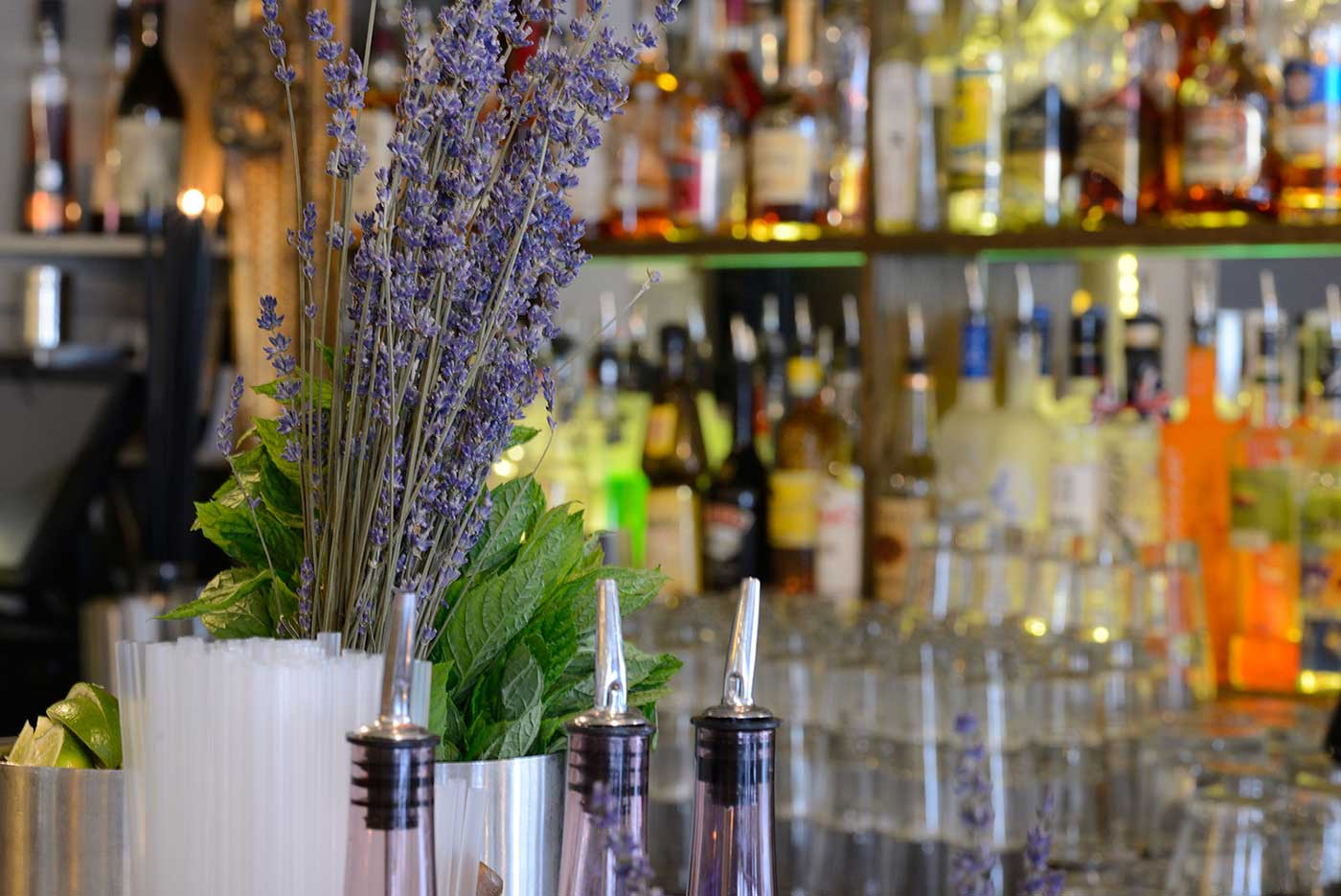 bar top featuring lavender, mint and limes. bottles in the background