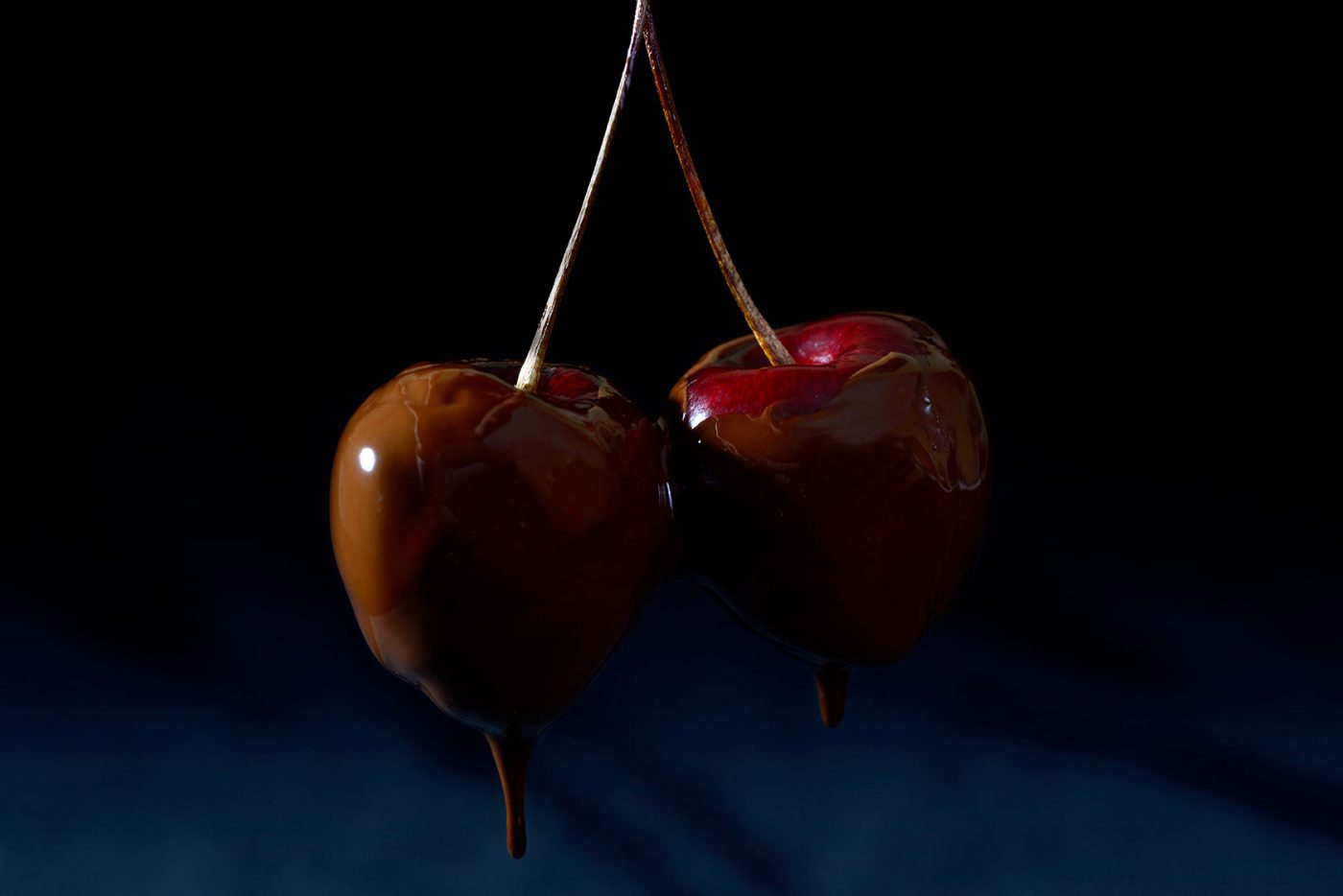 two fresh cherries dripping in chocolate
