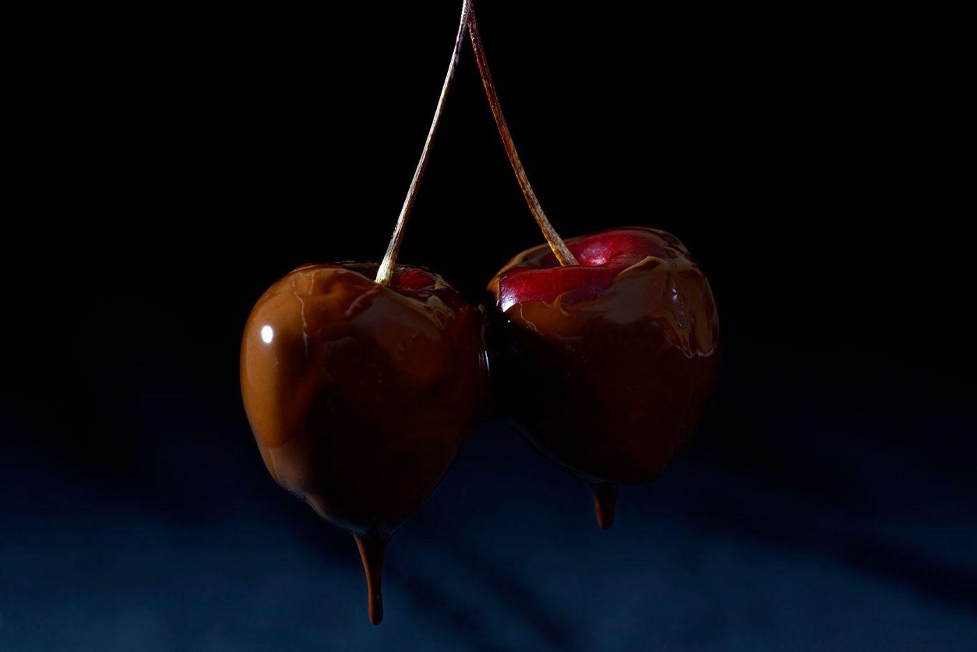 two fresh cherries dripping in chocolate