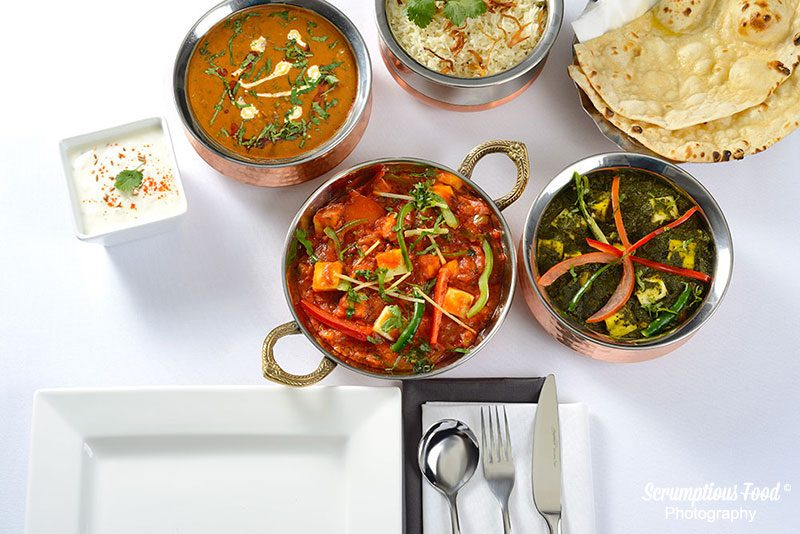 group of Indian curry dishes on a table
