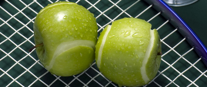apples cut to resemble tennis balls on a tennis racquet