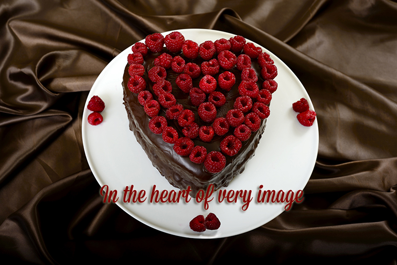heart shaped choclate cake topped with fresh raspberries set on a white plate with chocolate coloured satin in the background. Slogan In the heart of every image