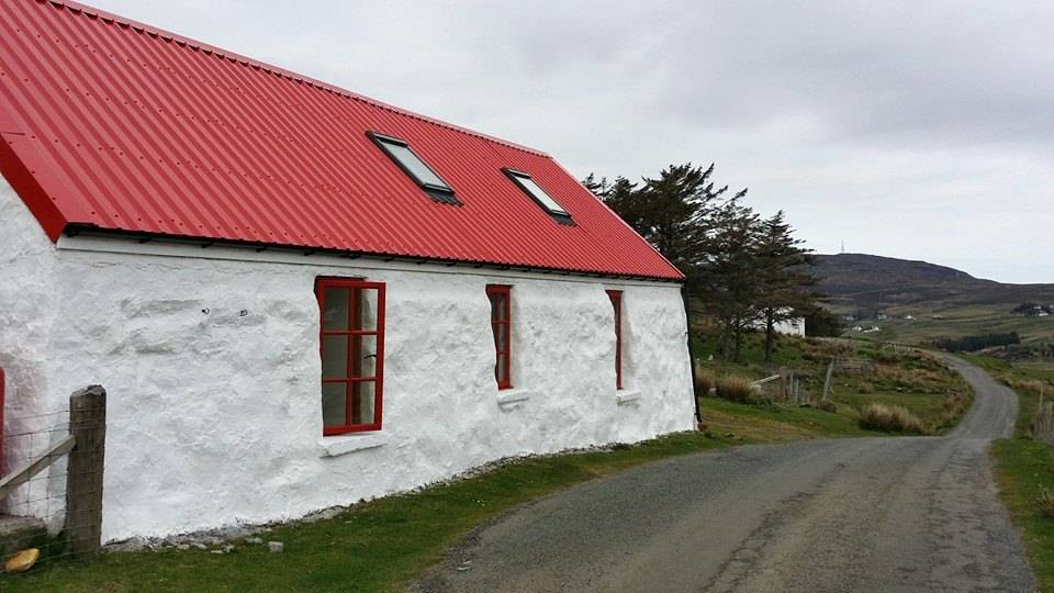 white stone wall cottage with corrugated iron roof painted red