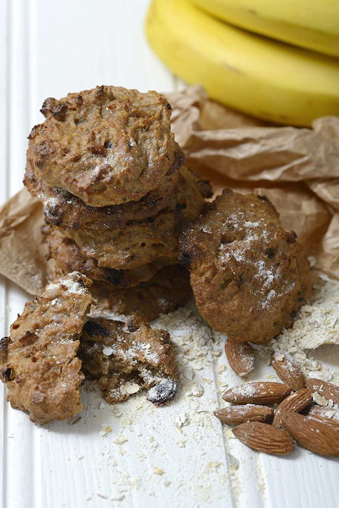 cookies on a white wooden background, brown paper bag, whole bananas, almonds, oats