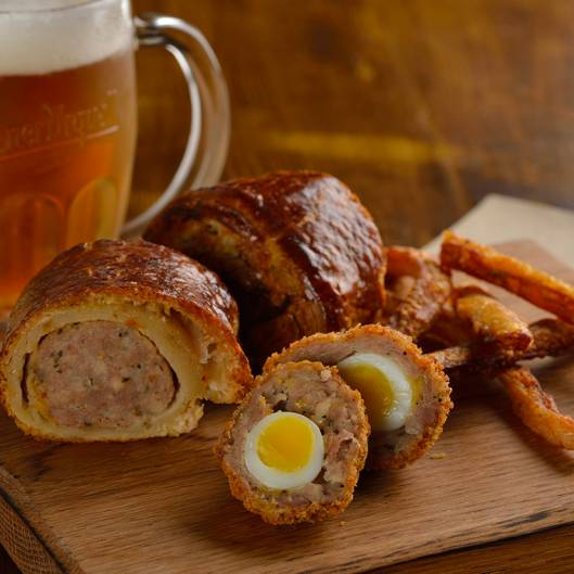 Scotch-egg, sausage-roll, pork-scratchings on a board served with a beer