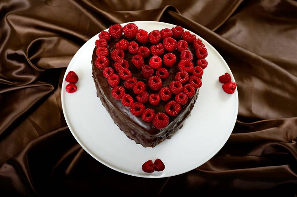 choclate heart shaped cake decorated with fresh raspberries