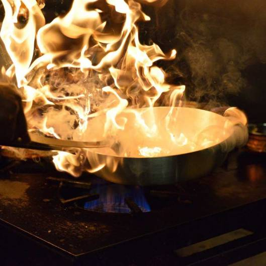 Cooking pan in a controlled flame on top of a gas hob