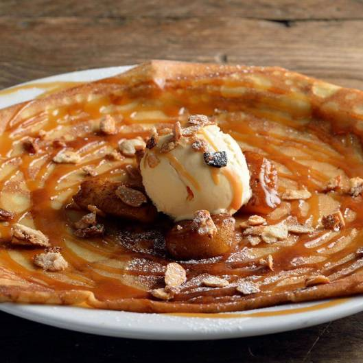 Crepe topped with vanilla ice cream, poached pear and sliced almonds