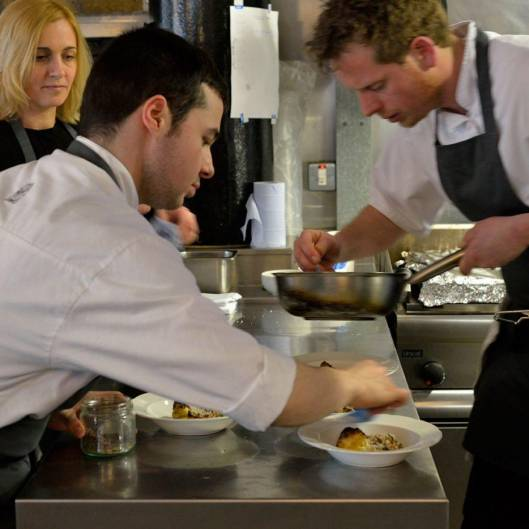 Chefs serving up plates of food at the pass.