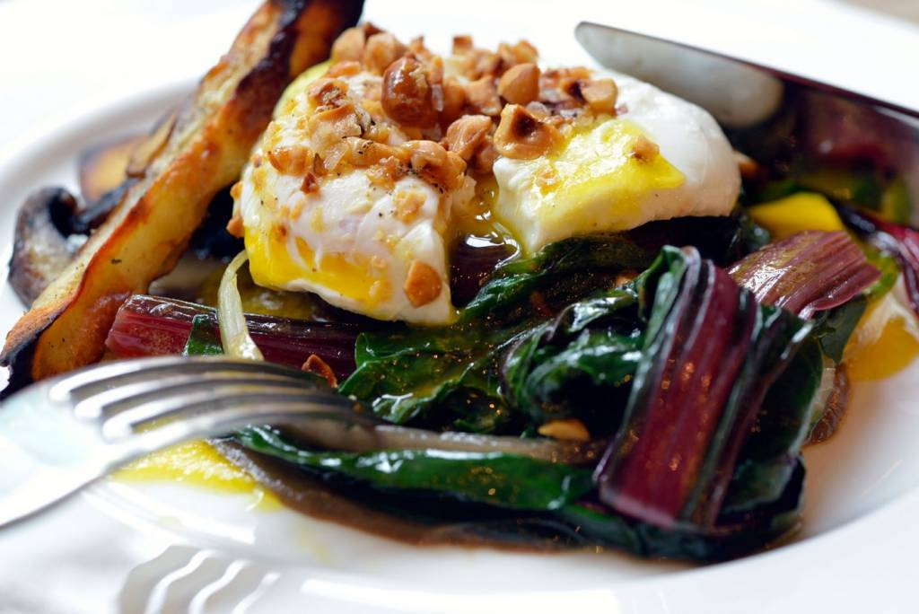 poached egg stuffed mushroom, rainbow chard, chopped nuts on a white plate